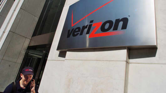 A pedestrian talks on his cell phone while walking past the Verizon Communications Inc. headquarters in New York.